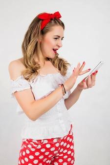 Красивая, привлекательная девушка играет на мобильном телефоне