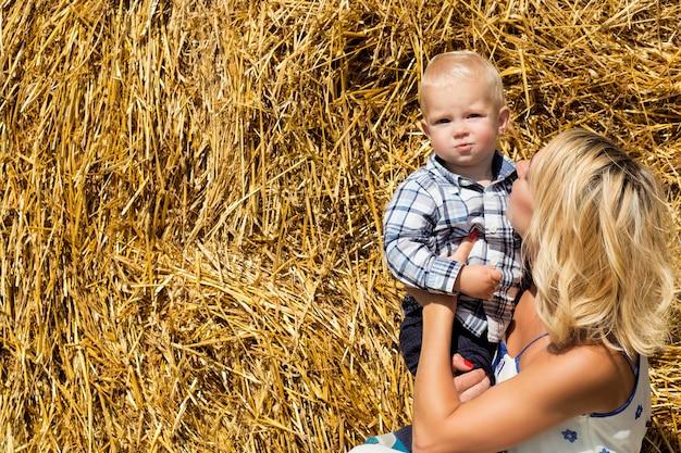 明るい晴れた日の干し草の山を背景にママと幼い息子が一緒に