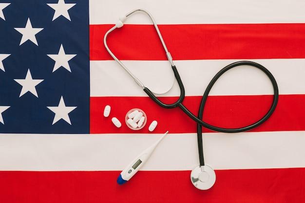 聴診器、薬と背景とコピースペースとしてアメリカの国旗に温度計の平らな医療コンセプトを置く