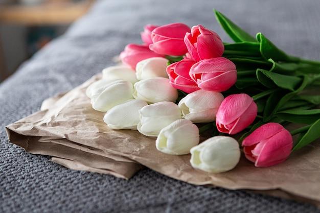 Свежий букет из белых и розовых тюльпанов на переработанной бумаге на сером фоне