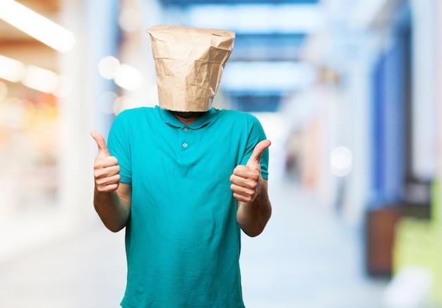 親指と彼の頭の上の紙袋を持つ男