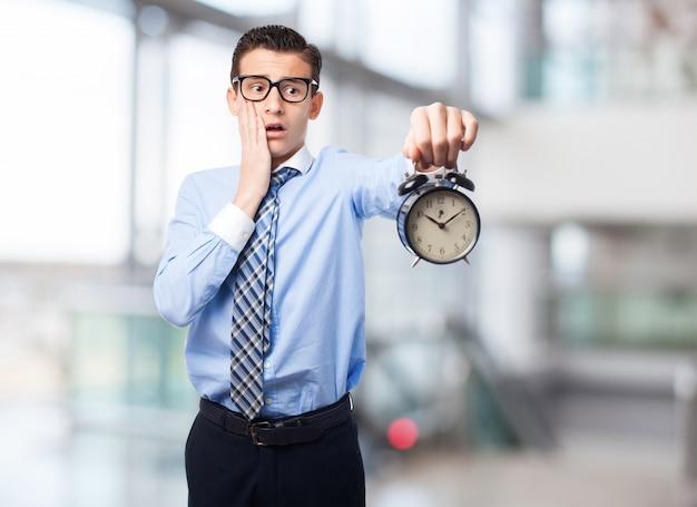 目覚まし時計を持つ男
