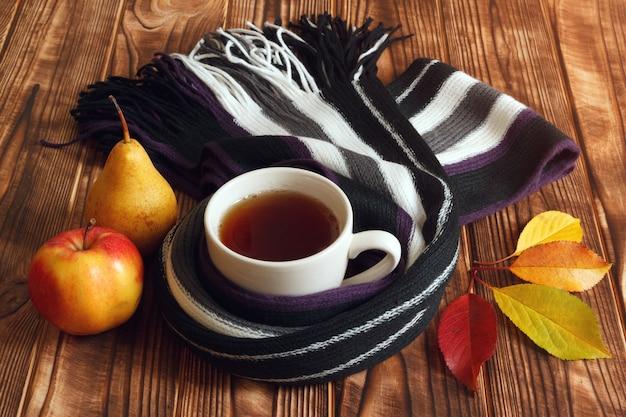 秋のお茶、果物、木製の背景の葉