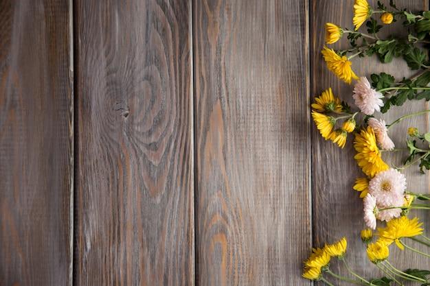秋の背景。茶色の木製の背景の花。