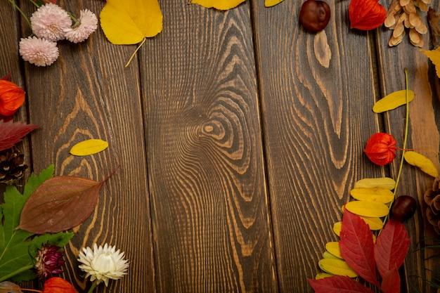 秋の背景。明るいオレンジ色の果実、非常に花と茶色の木製の背景の葉。