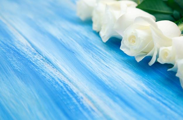 ホワイトローズ。木製の青い背景に繊細なバラの花束