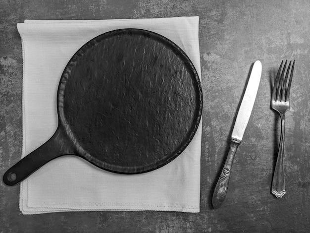 灰色の石のコンクリートテーブルの背景にナイフとフォークで空の白いセラミックプレート。コピースペース。メニューレシピコンセプト