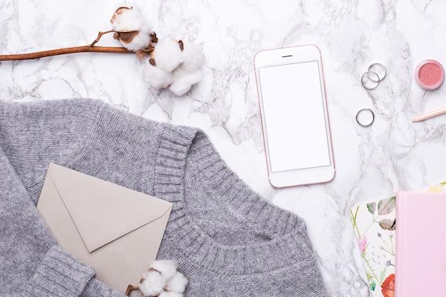携帯電話とコットンの花と居心地の良いグレーのセーター