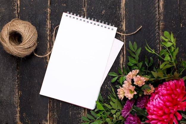 暗いヴィンテージの木の花の花束とメモ帳