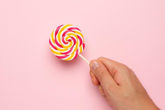 ピンクの手でカラフルなロリポップ