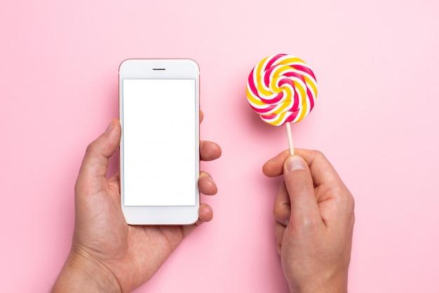 カラフルなロリポップとピンクの手で携帯電話