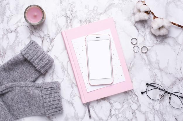 Женский рабочий день с мобильным телефоном и розовой тетрадью на мраморном столе