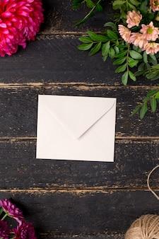 暗いビンテージテーブルの上の美しい花と封筒