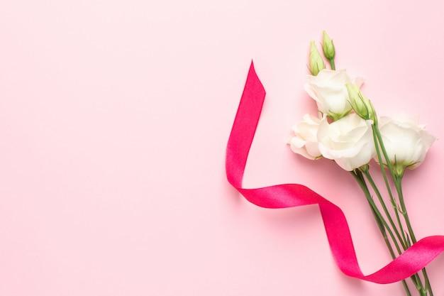ピンクのギフトリボンフクシア色と白い花