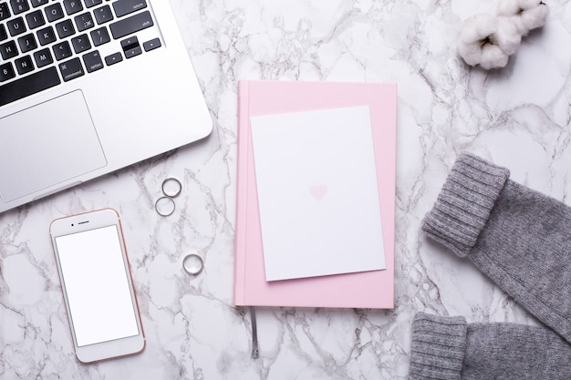携帯電話、キーボード、大理石のテーブルの上のピンクのノートブックと女性営業日