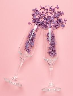 ピンク色の紙ミニマルスタイルのライラック色の花とシャンパングラス。夏休み。