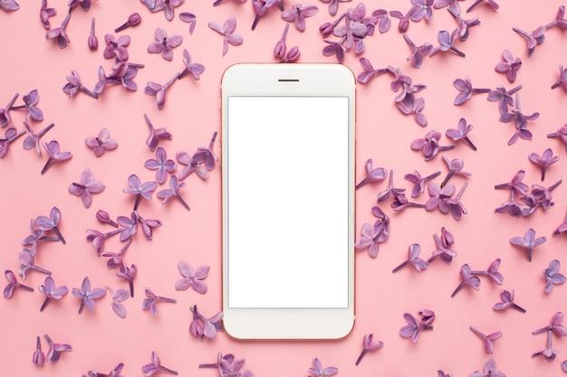 フラットレイアウトスタイルのピンクのパステル調のテーブルに携帯電話のライラック色の花。女性作業机。ファッションカラー