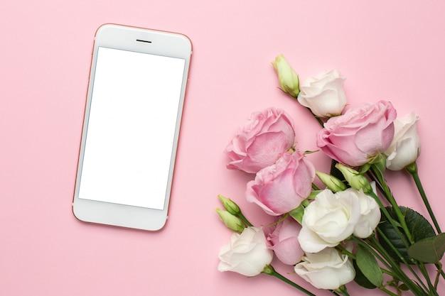 ピンクと白のバラの花を持つ携帯電話。休日、バレンタインデー、女性の日の最小限の構成。