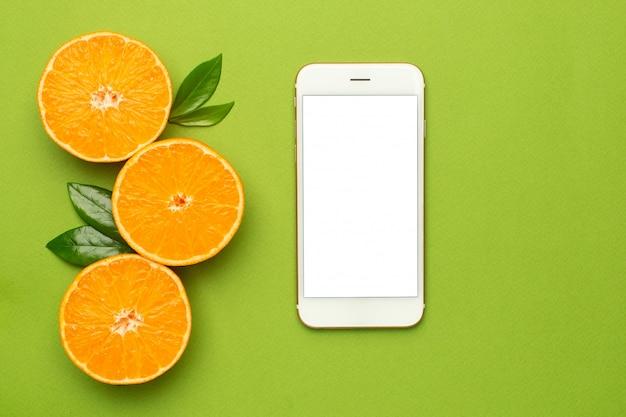 携帯電話とタンジェリン、フルーツフラットレイ、夏の最小限の構成