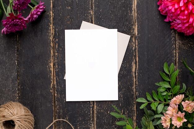 Белая подарочная карта с красивыми цветами на темном старинном столе