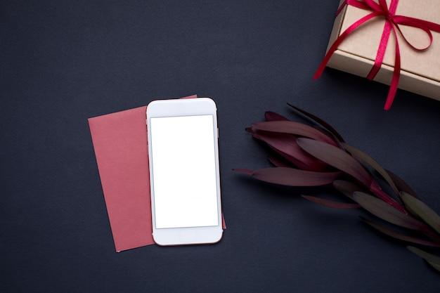 Мобильный телефон и с цветком и подарок на темном
