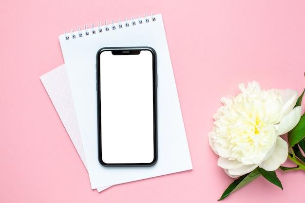 携帯電話のモックアップ、ピンクのパステル調のテーブルの上のノートブックと牡丹の花。女性作業机。サマーカラー