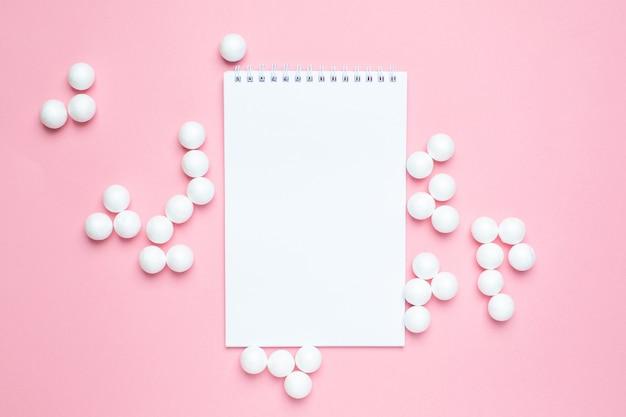 Бизнес блокнот и белые пластиковые шарики на розовом