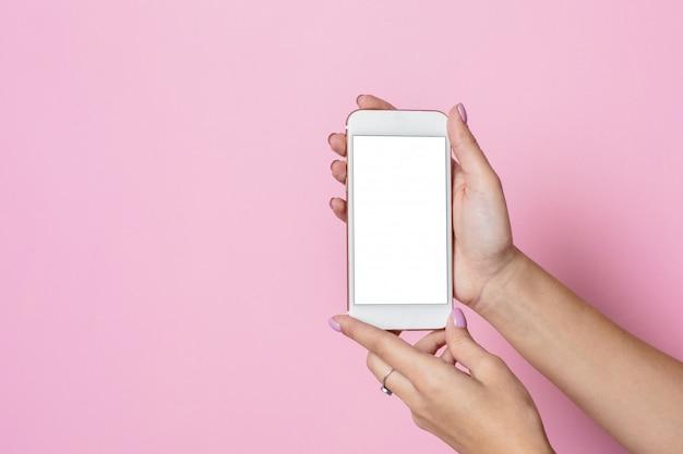 Женские руки держат мобильный телефон с белым экраном на розовой поверхности