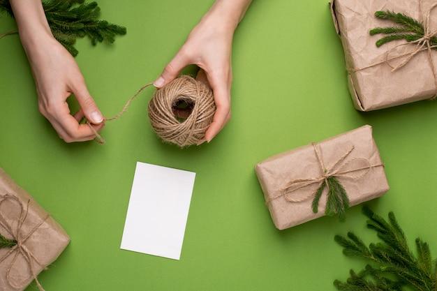 手のエコひもと緑の表面にペーパークラフトの緑の植物との贈り物