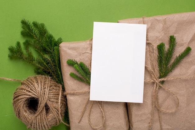 緑の表面にペーパークラフトのエコプレゼントと緑の植物のカード