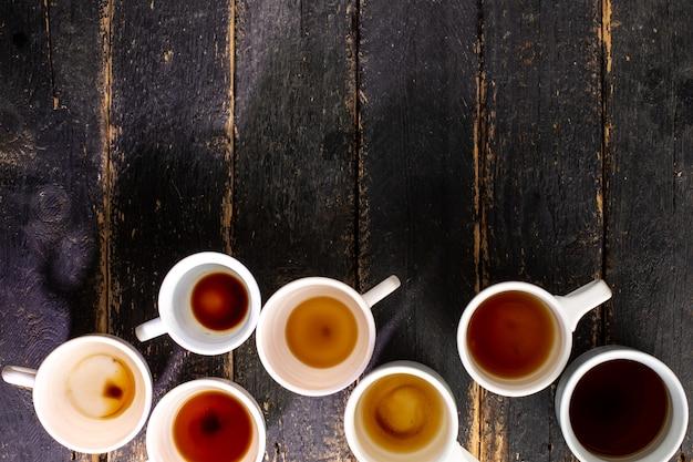テキスト用のスペースを持つ木製のテーブルの上のコーヒー残渣と白いカップ。