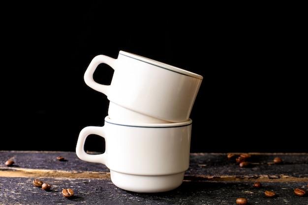 木製のテーブルとテキスト用のスペースと黒の背景に白いコーヒーマグカップ。