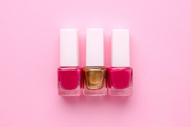Косметические розовые и золотые лаки для ногтей на розовом