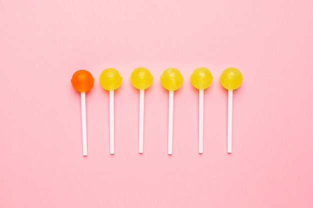 Сладкие желтые и оранжевые конфеты леденец на пастельно-розовый. минималистская композиция.