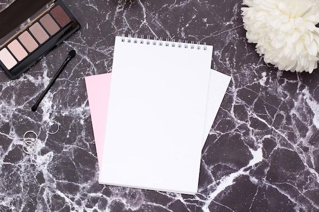 黒い大理石のテーブルに女性用ノートと化粧品