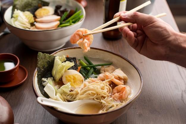 エビと麺のレストランでアジアのラーメンを食べる男