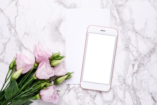 大理石のピンクの花と携帯電話
