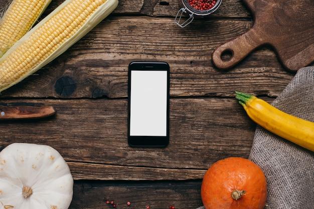 秋野菜:白い空の画面、カボチャ、木の上の黄色の葉とトウモロコシの携帯電話