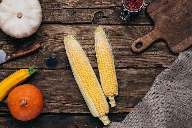 秋野菜:カボチャとトウモロコシの黄色の葉と木のカットボード