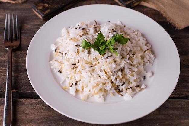 木製テーブルの上の白い皿にハーブとバスマティ米