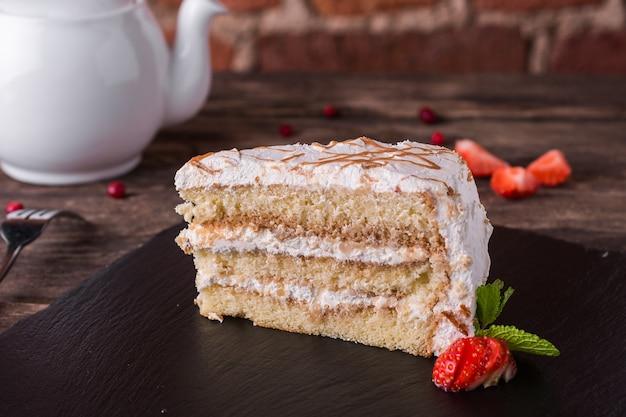 Бисквитный торт с кремом и карамелью на каменной плите на деревенском деревянном столе