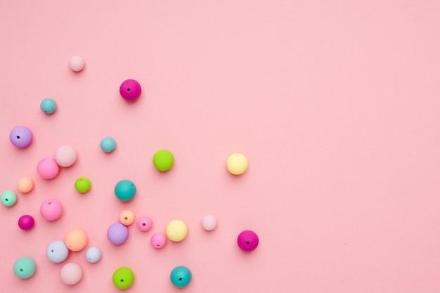 ピンクの背景。カラフルなパステルビーズ。ガーリーなミニマリストの構成