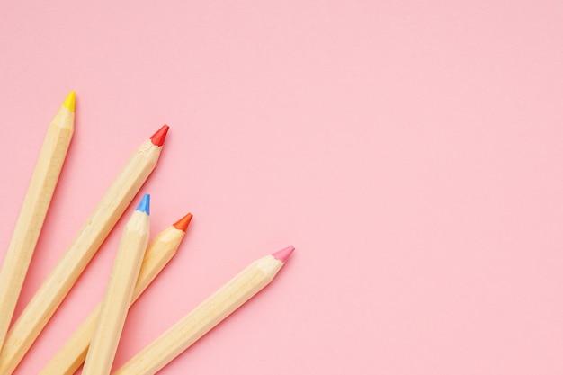木製のカラフルな普通の鉛筆とピンクの背景。学校に戻る。