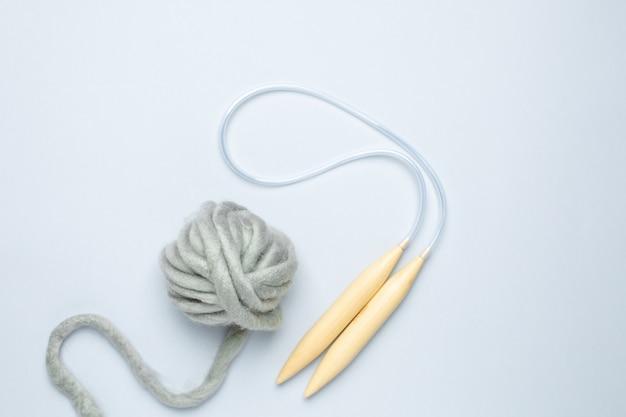 丸編み針と青の背景に太い灰色の糸