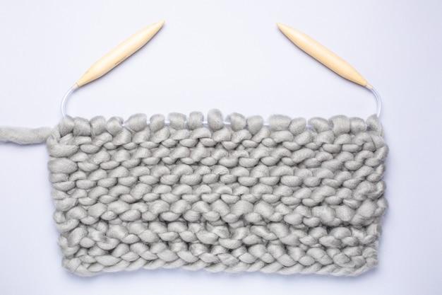 編み物プロジェクトが進行中です。糸の玉と編み針で編む一片。