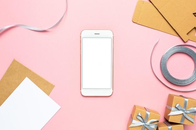 ピンクの背景の誕生日のボックス構成のギフトと携帯電話