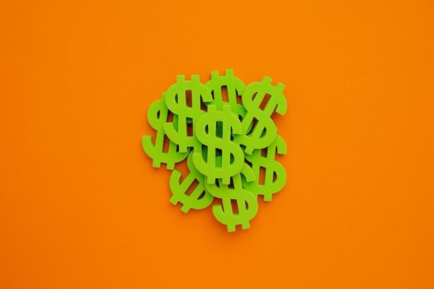 オレンジ色の背景にアメリカのドル記号。グリーンマネーフラットレイ