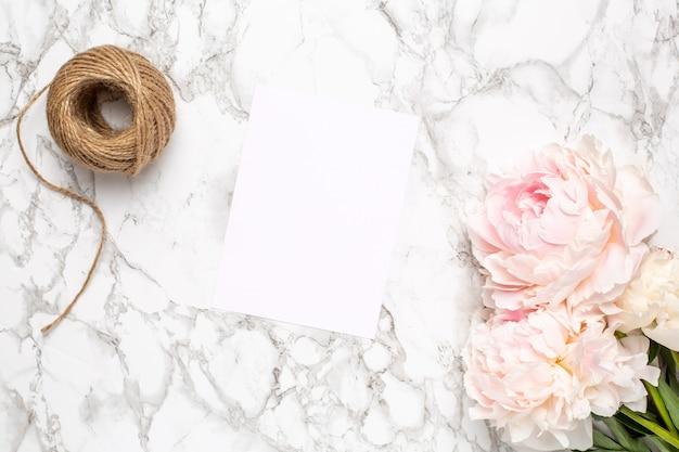 大理石の表面にグリーティングカードとピンクの花牡丹。休日と夏のアイテム。