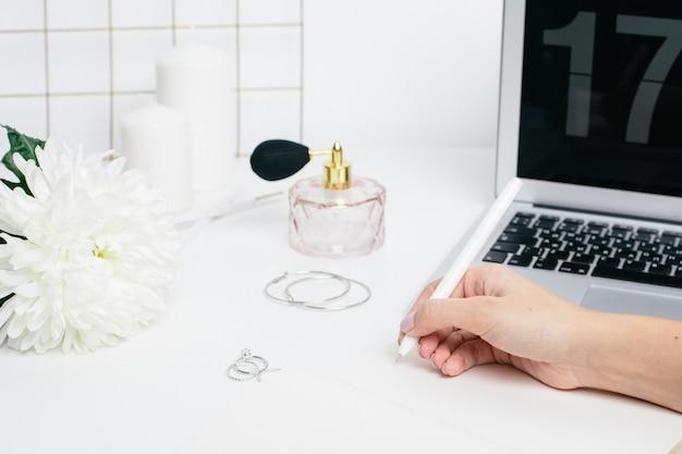 ノートパソコンのキーボードで白いテーブルにメモ帳でメモを作る女性の手