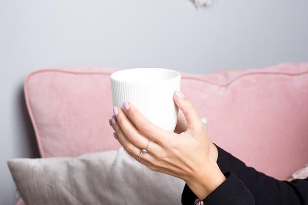 女性の手はピンクのインテリアで白いセラミックマグカップでお茶を保持します。